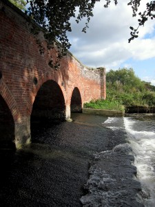 view across river weir, bridge and far bank
