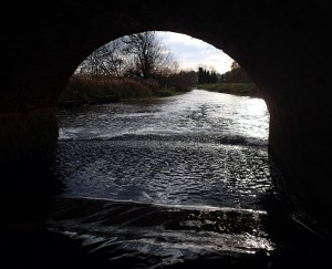 view through rounded arch of bridge downstream weir and river