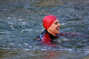 woman in wetsuit and swim hat in choppy water