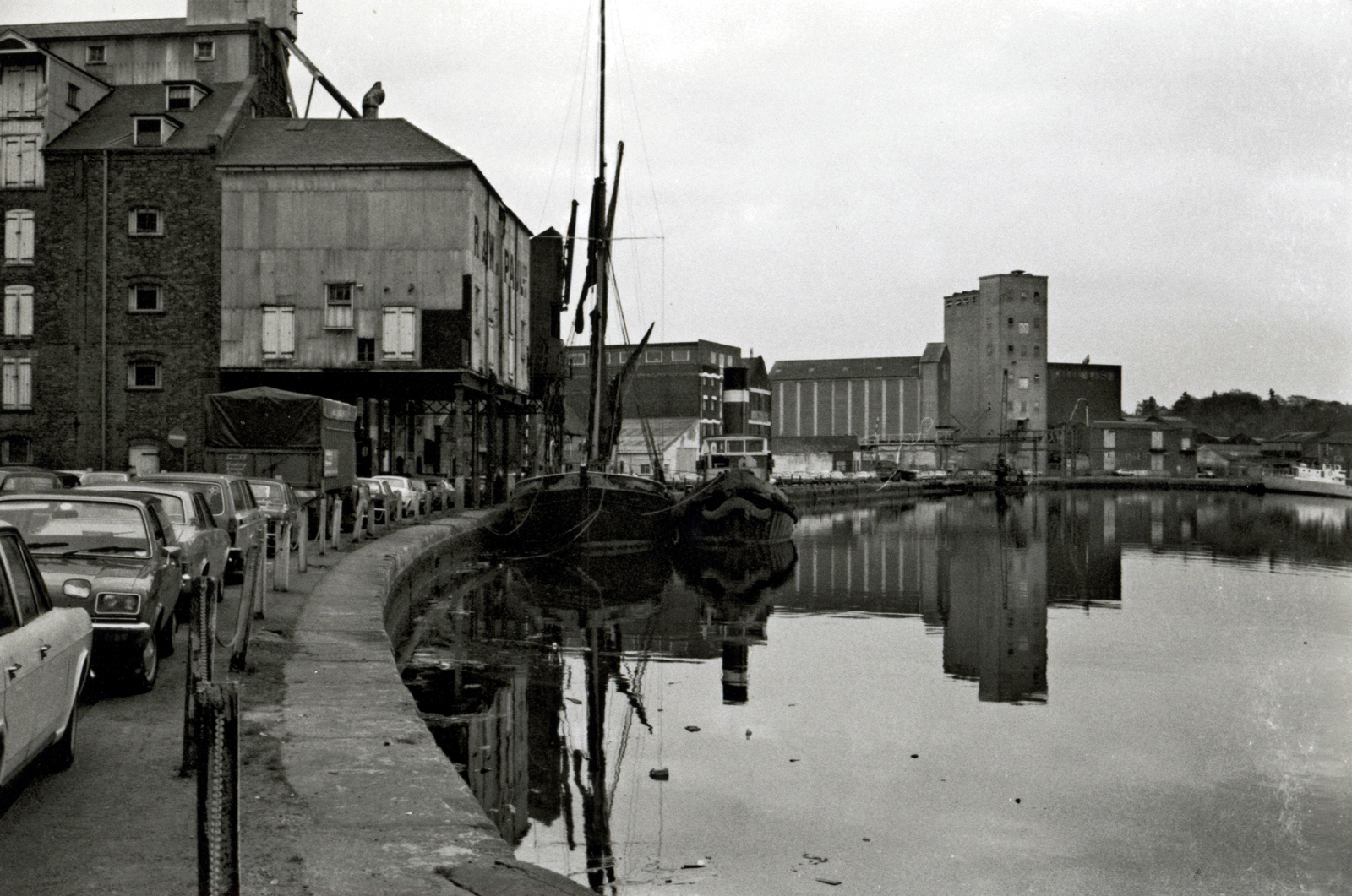 Black & white photo of dock buildings and boat reflected in water