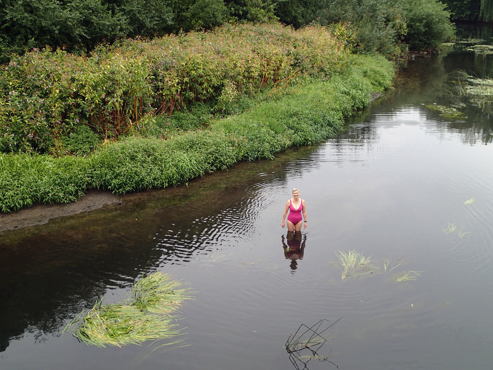 woman standing in river with reflection and bank foliage behind