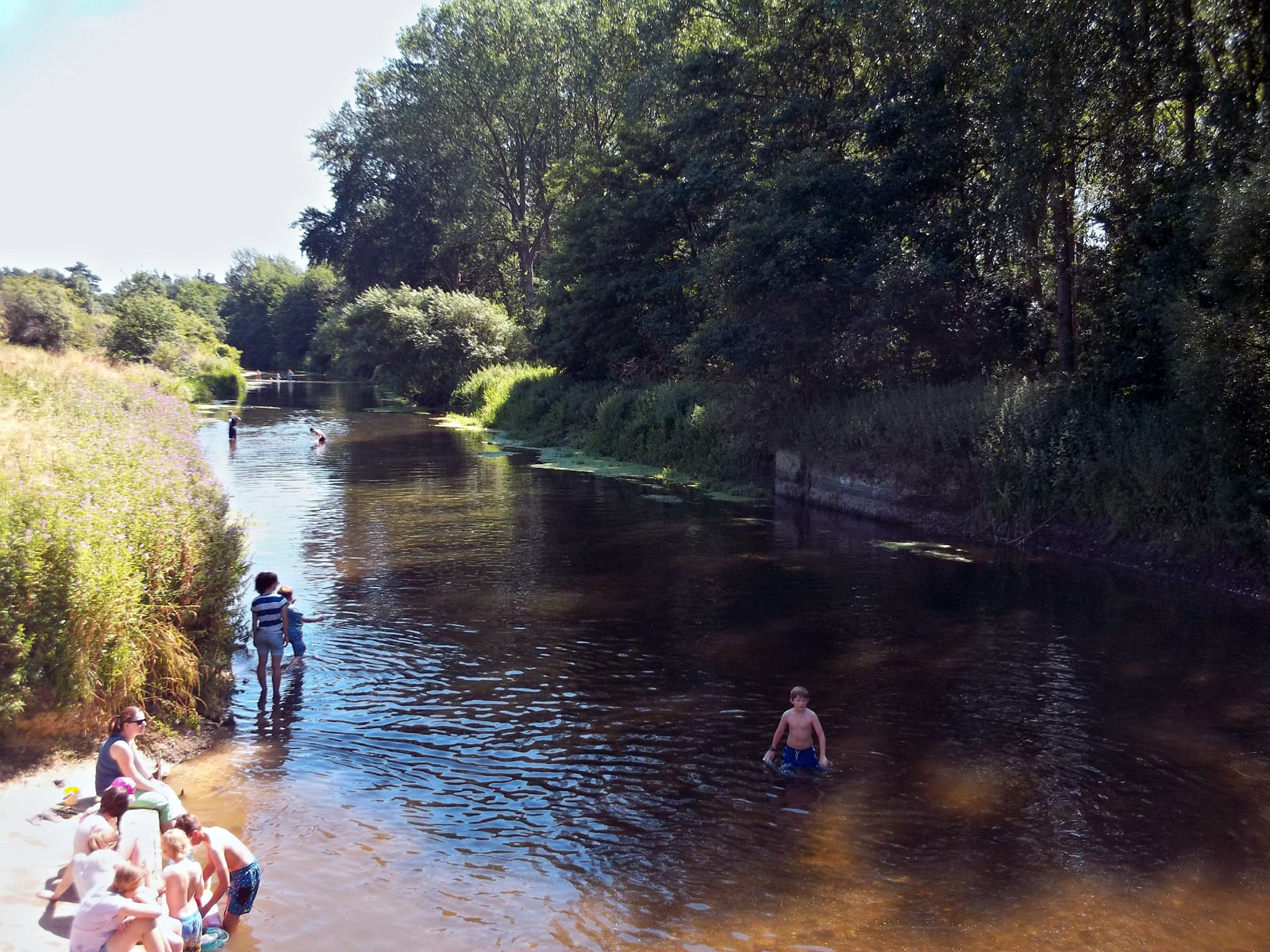children in the river with a family sitting on the edge