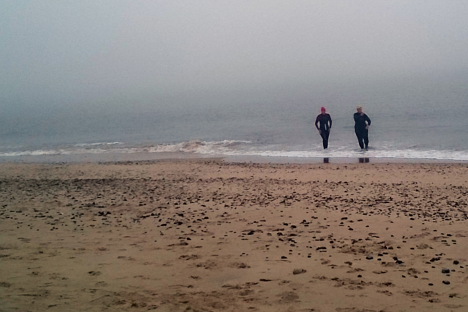 Two wetsuited swimmers on beach in fog