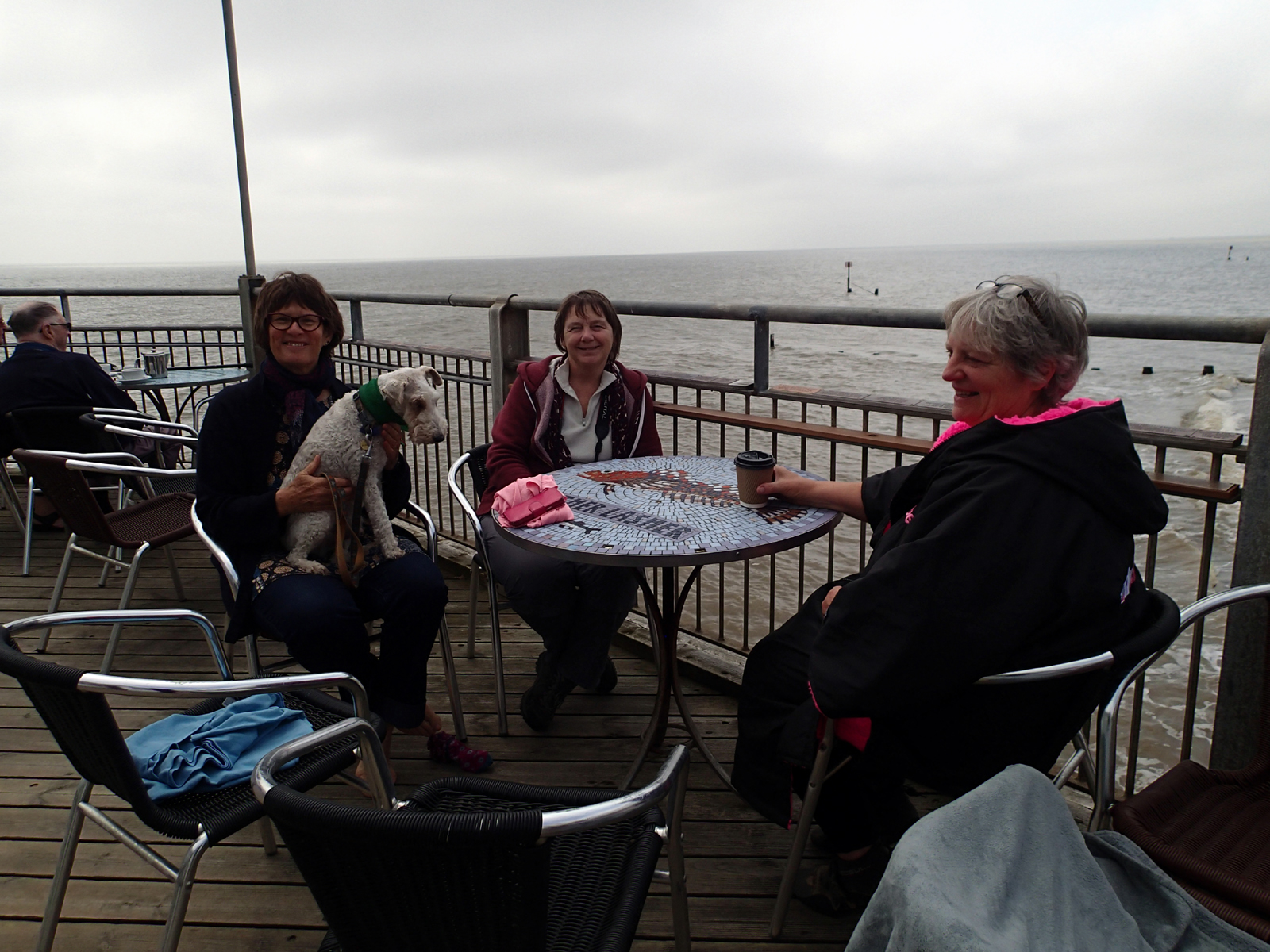 3 supporters and sister swimmers (one with dog) sit at table on pier