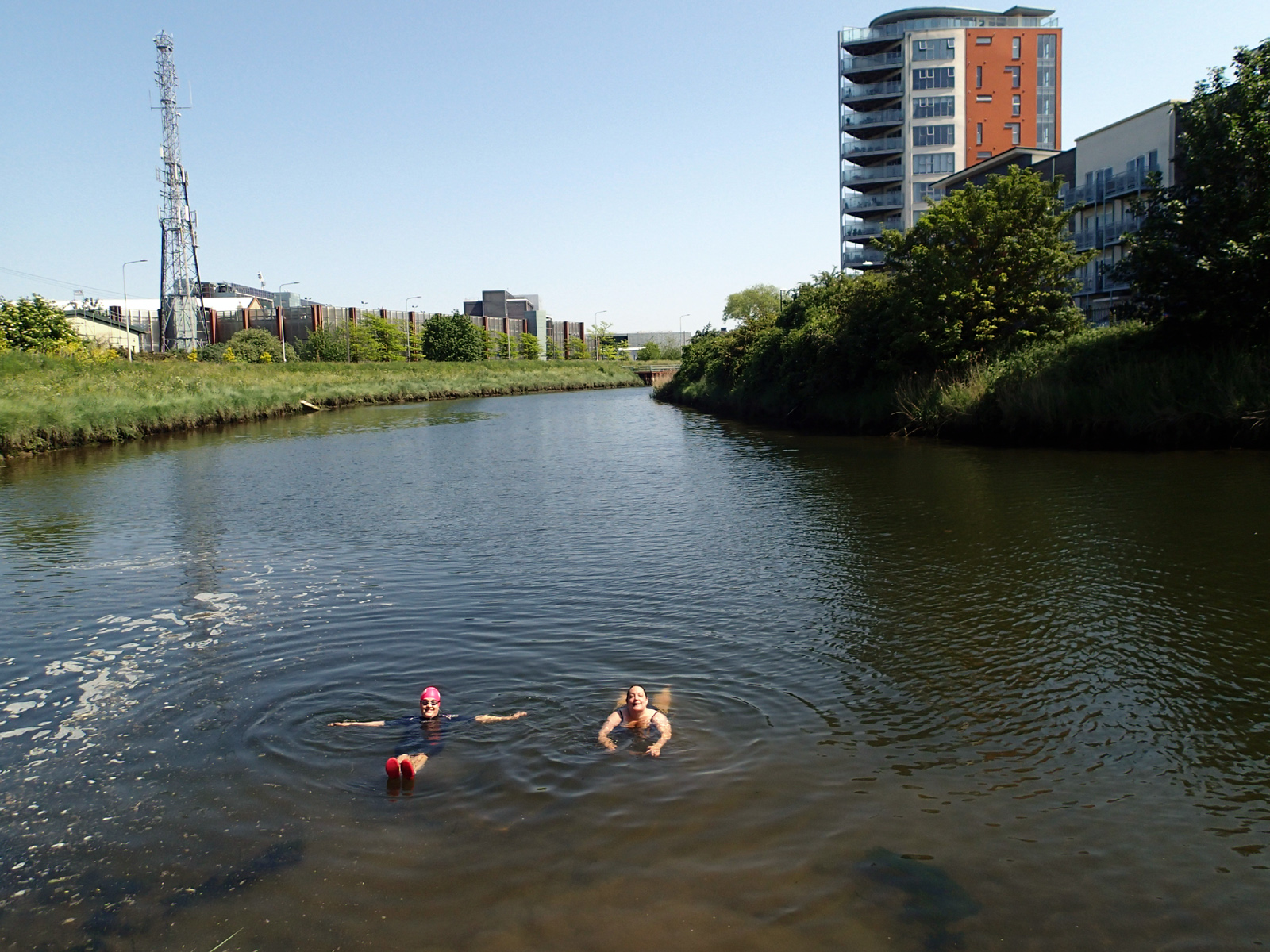 two women swimming in river with grassy banks and buildings in background