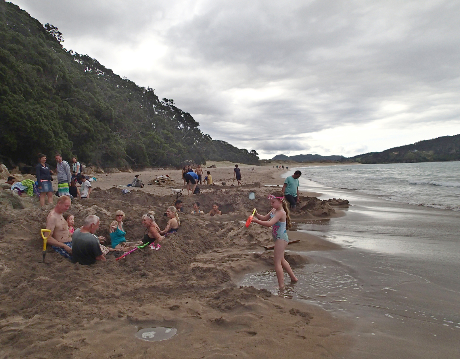 beach with children and adults in holes dug in sand, with sea