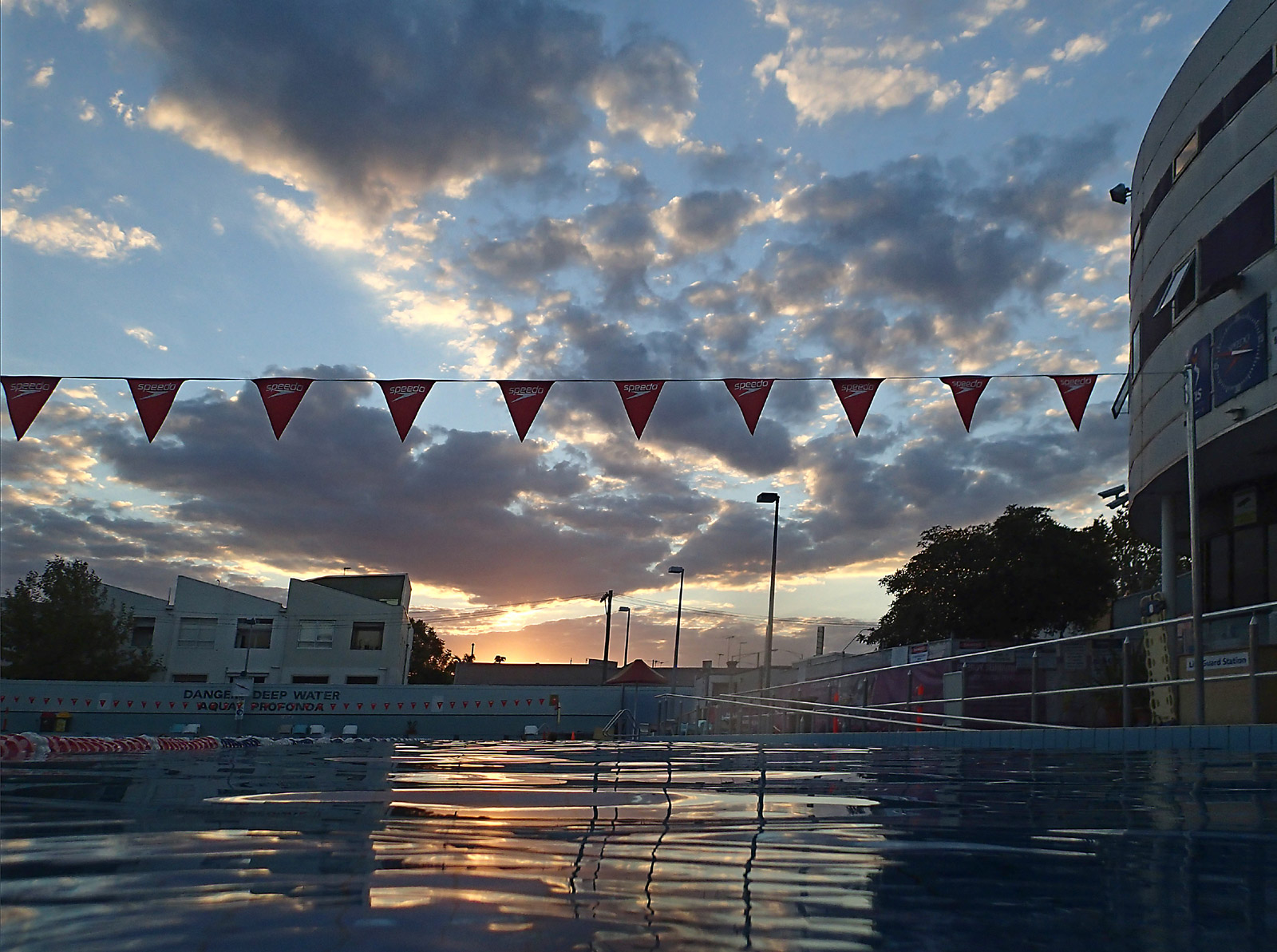 Outdoor swimming pool with sun setting