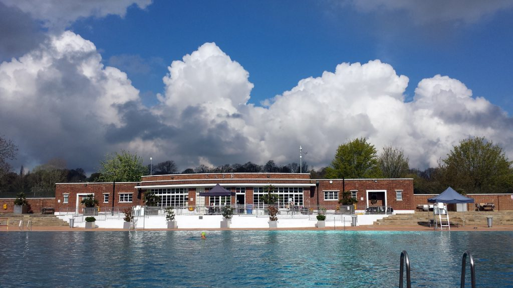 outdoor pool with art deco building and dramatic clouds