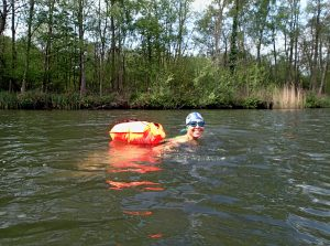 swimmer in river with orange float