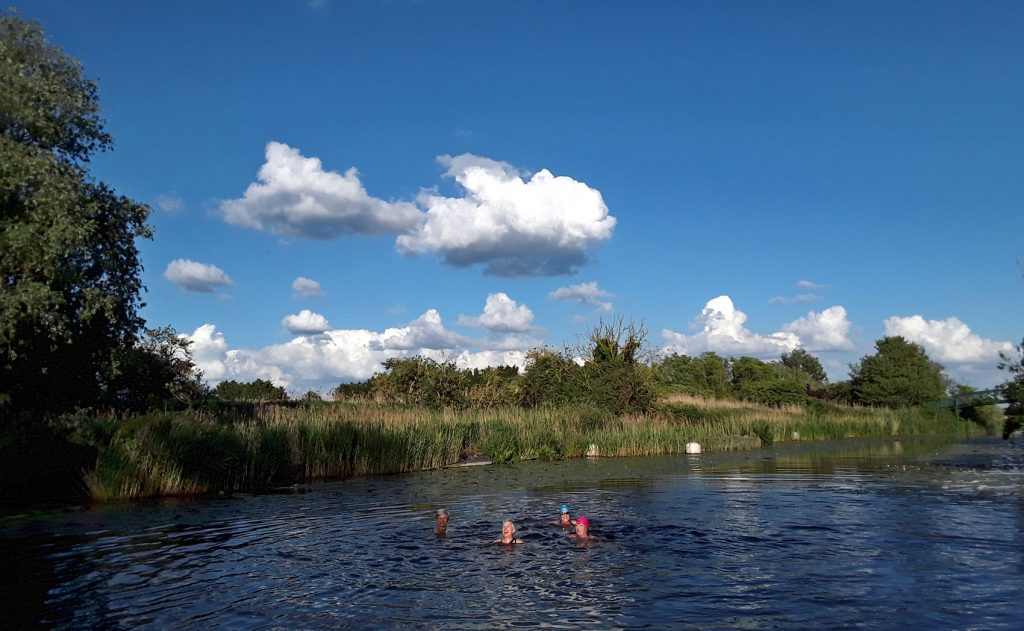 swimmers in river, blue sky