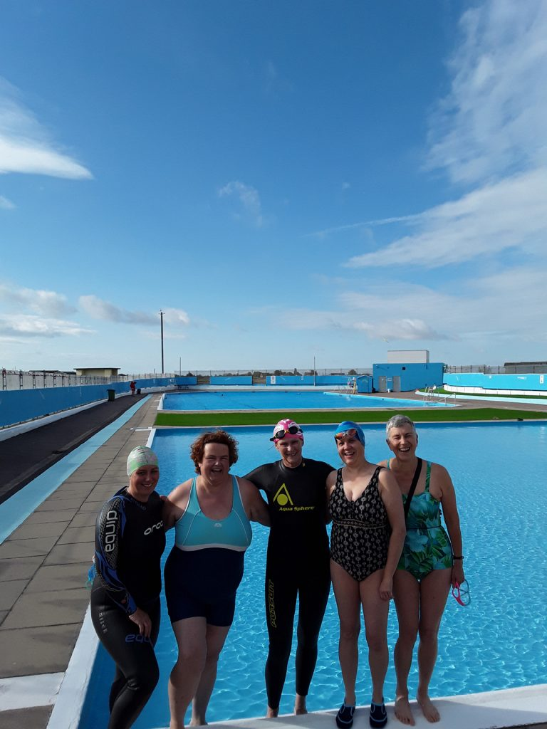 five swimmers in front of an open air pool