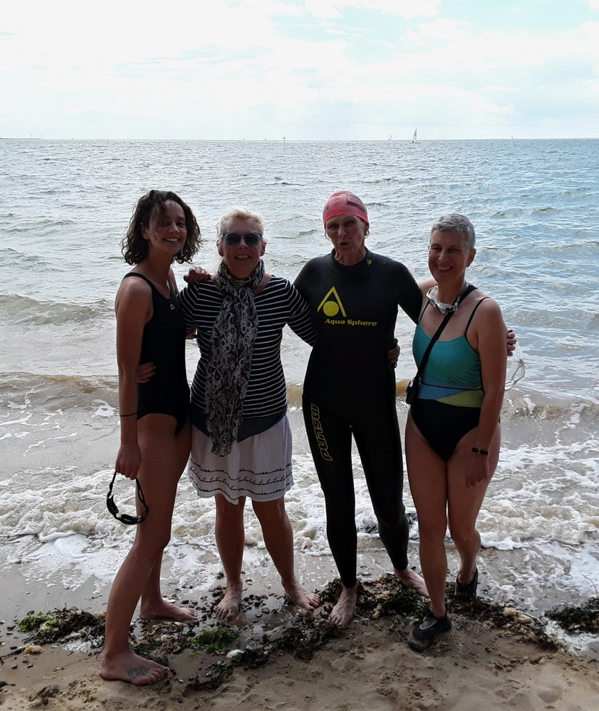 four swimmers in front of the sea