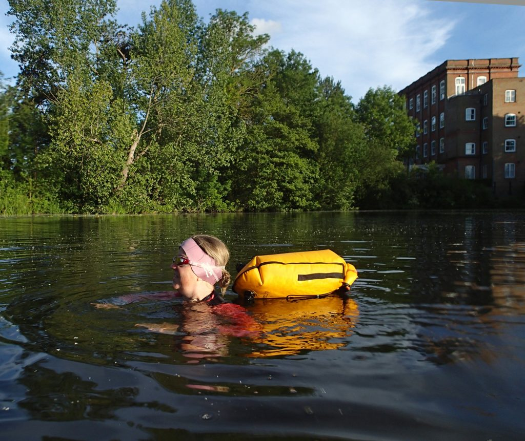 swimmer in mill pond and building