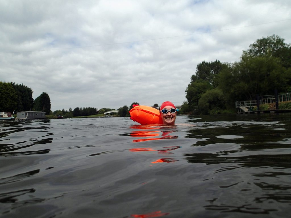 swimmer with tow float and moored boat behind