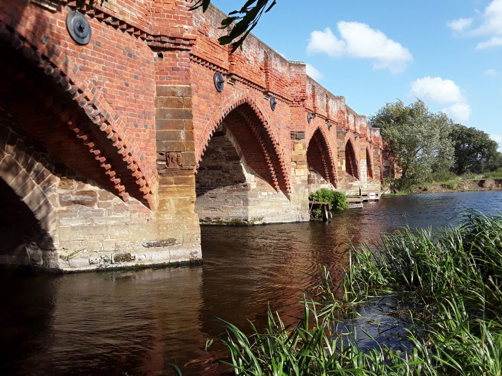 old brick bridge and river