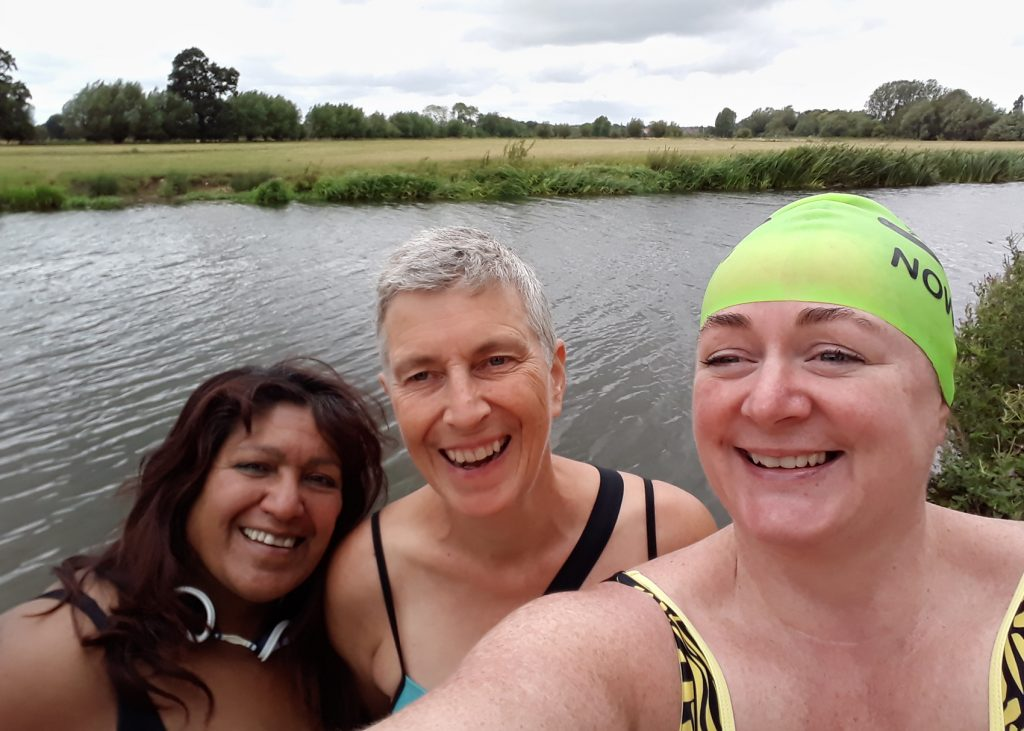 three swimmers in a river