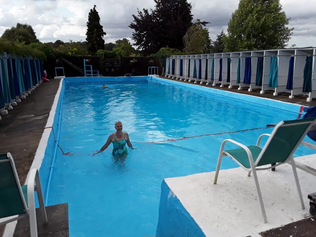 swimmer in lido with changing cubicles around