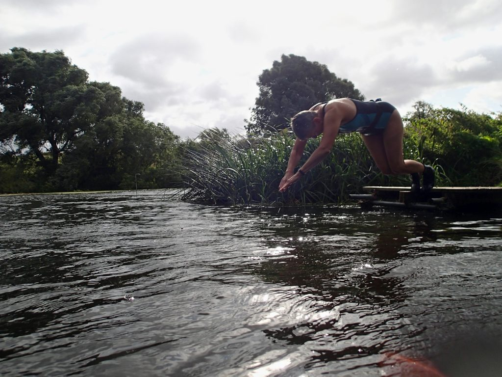 swimmer diving into river