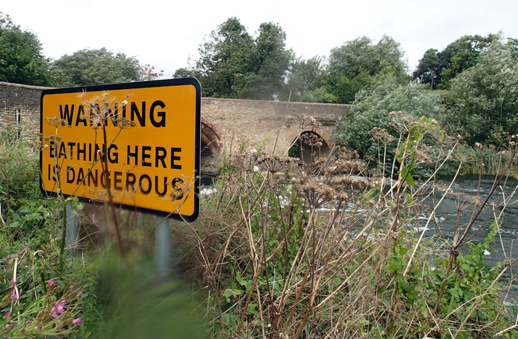 Warning Bathing Here Is Dangerous sign with old bridge and river