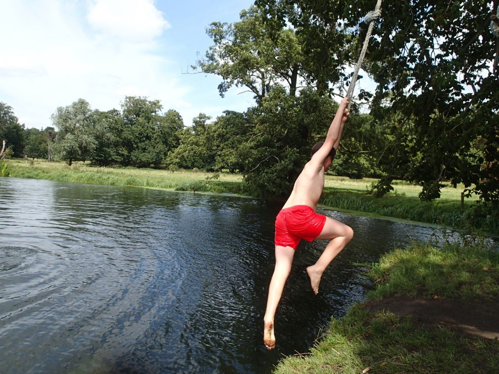 boy on rope swing over river