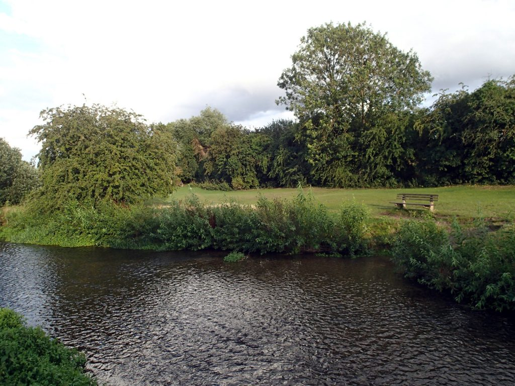 shallow river, field and bench