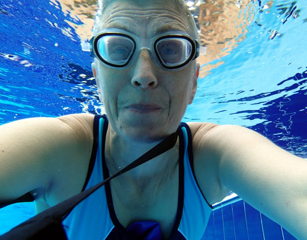 swimmer with goggles underwater with blue tiles