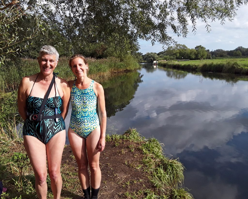 two swimmers on the bank of a river