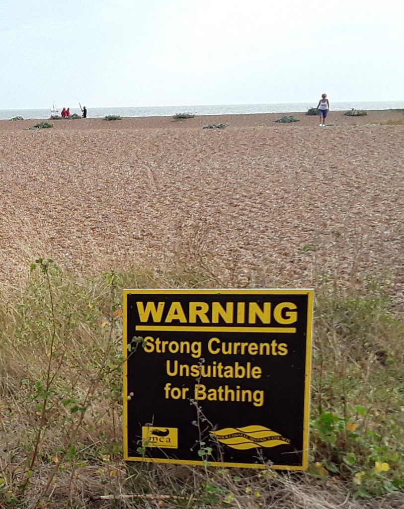 warning sign about dangerous currents, and beach