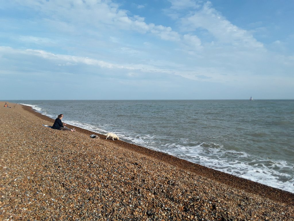 steep shingle slope with fisherman and sea