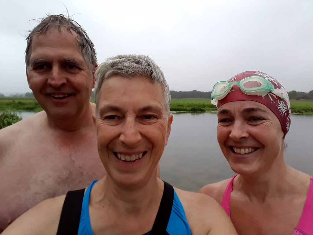 three swimmers selfie and water