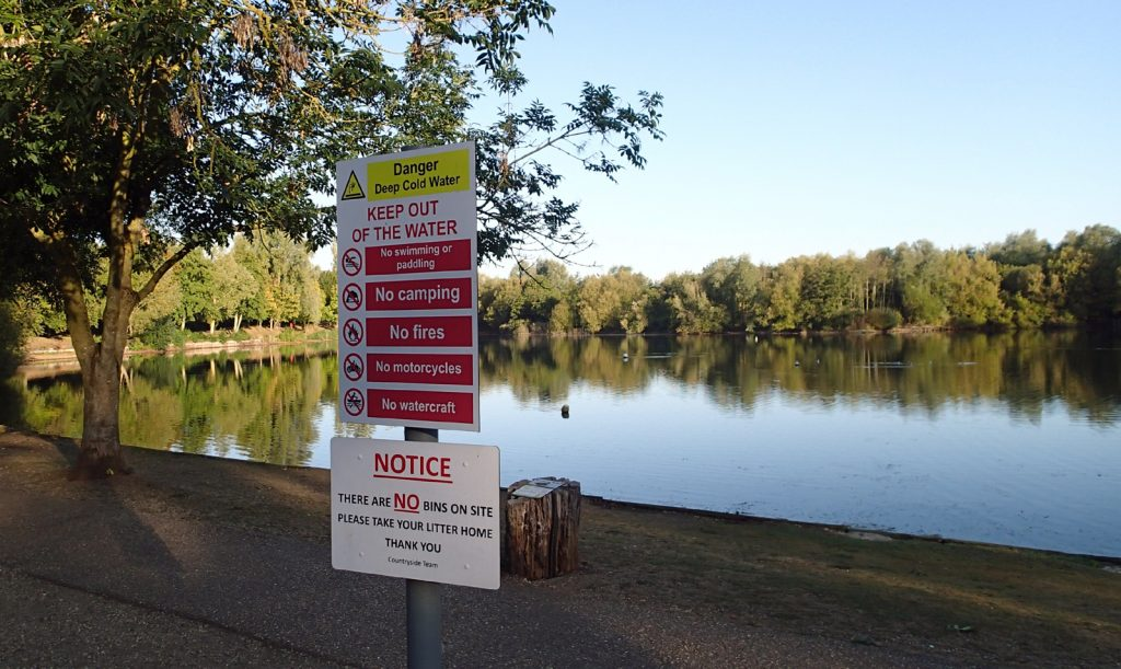 sign, many activities including swimming prohibited, lake with sunlit foliage