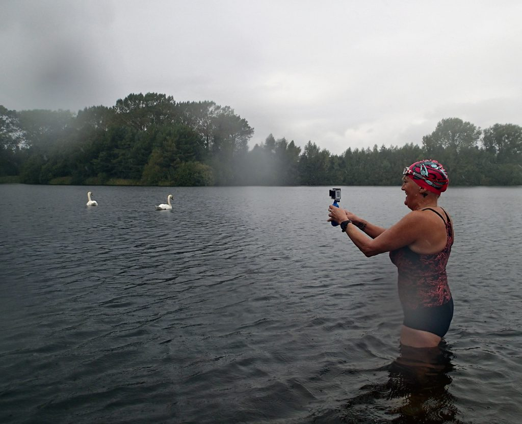 swimmer with camera, water, swans