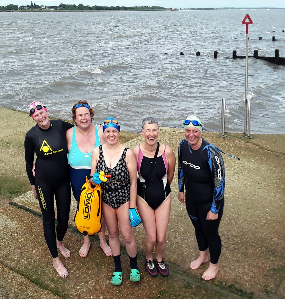 5 swimmers in front of sea