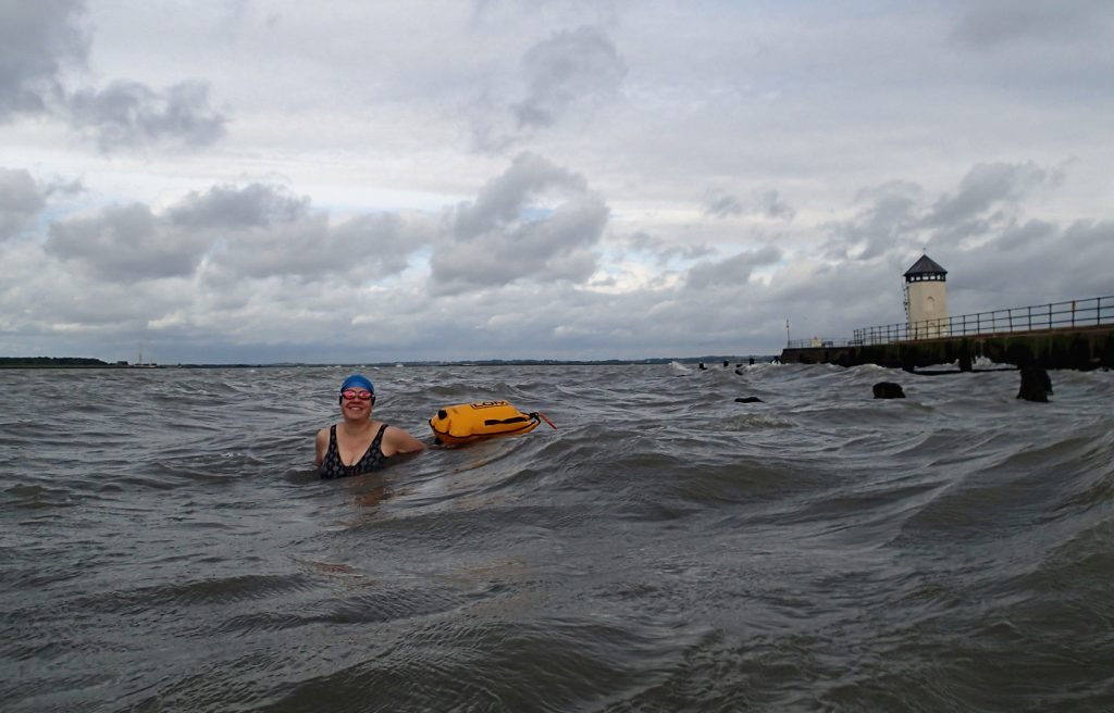 swimmer in sea, groynes and Bateman's Tower