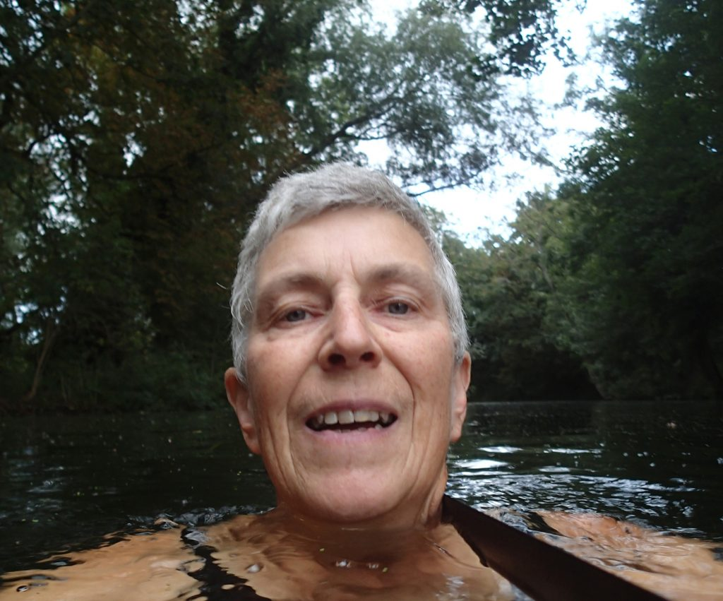 swimmer in water with trees