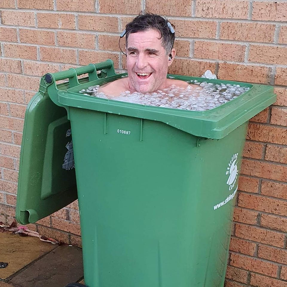 man in wheelie bin full of ice and water