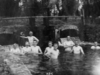Black and white photo of men bathing in a river pool