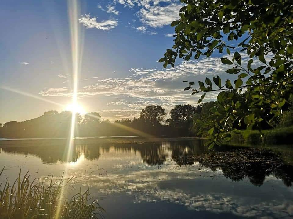 lake with sunburst, reflected clouds and trees