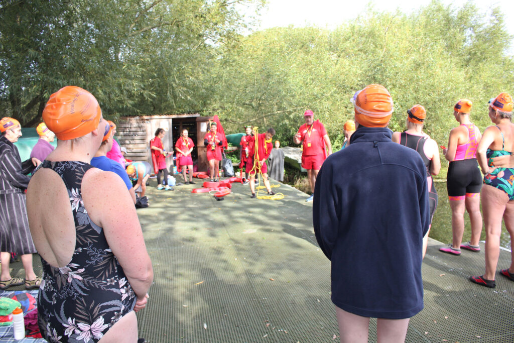 group of swimmers listening to trainer