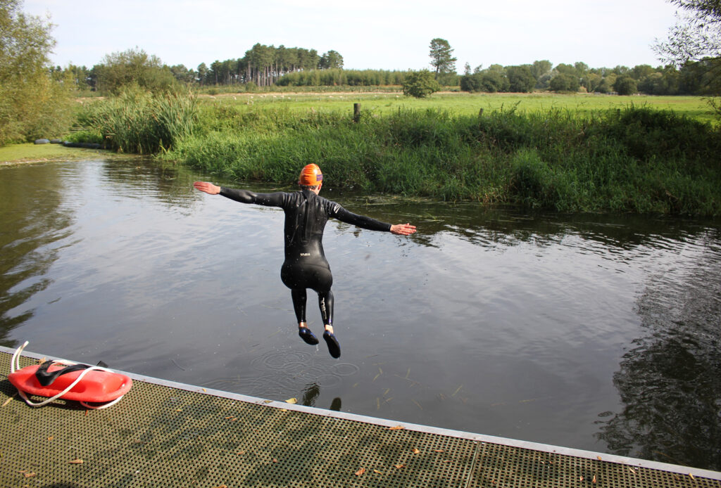 wetsuited swimmer jumping into the water