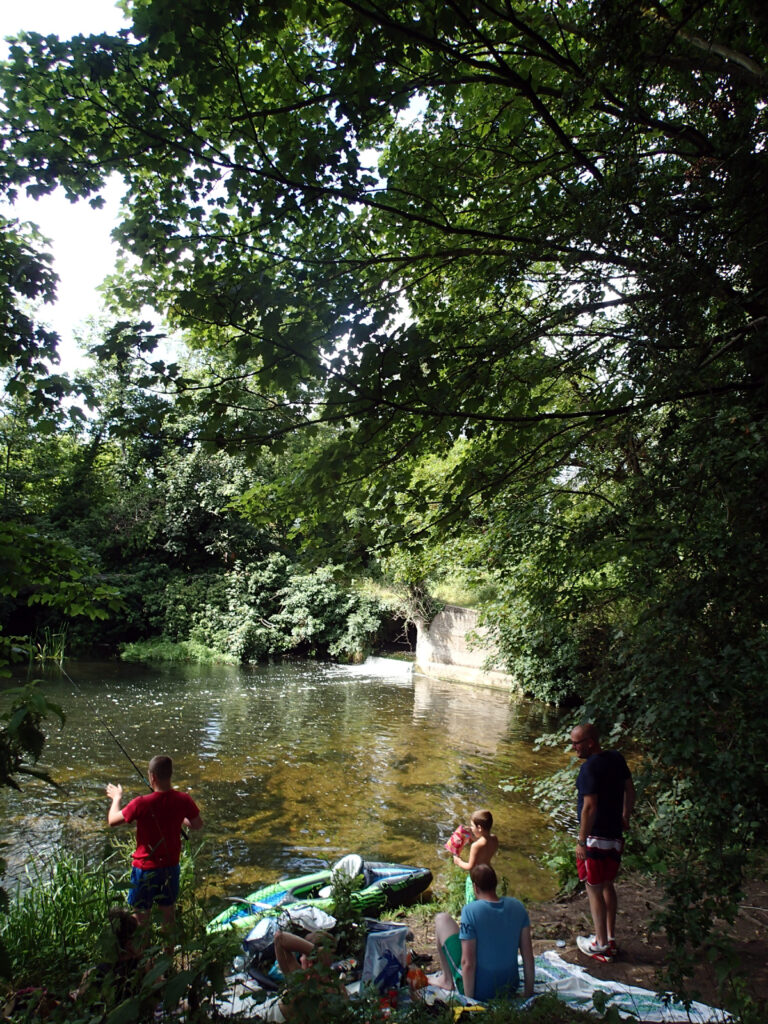 family with picnic and kayak by river pool