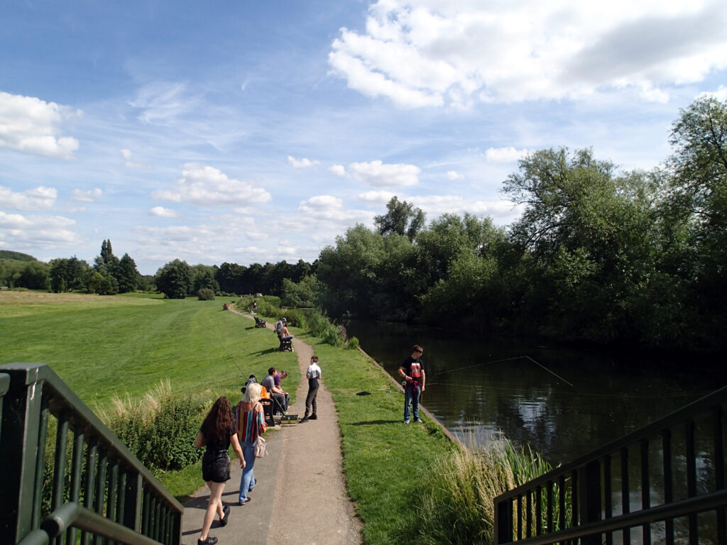 river and meadow, with people fishing, walking, chatting