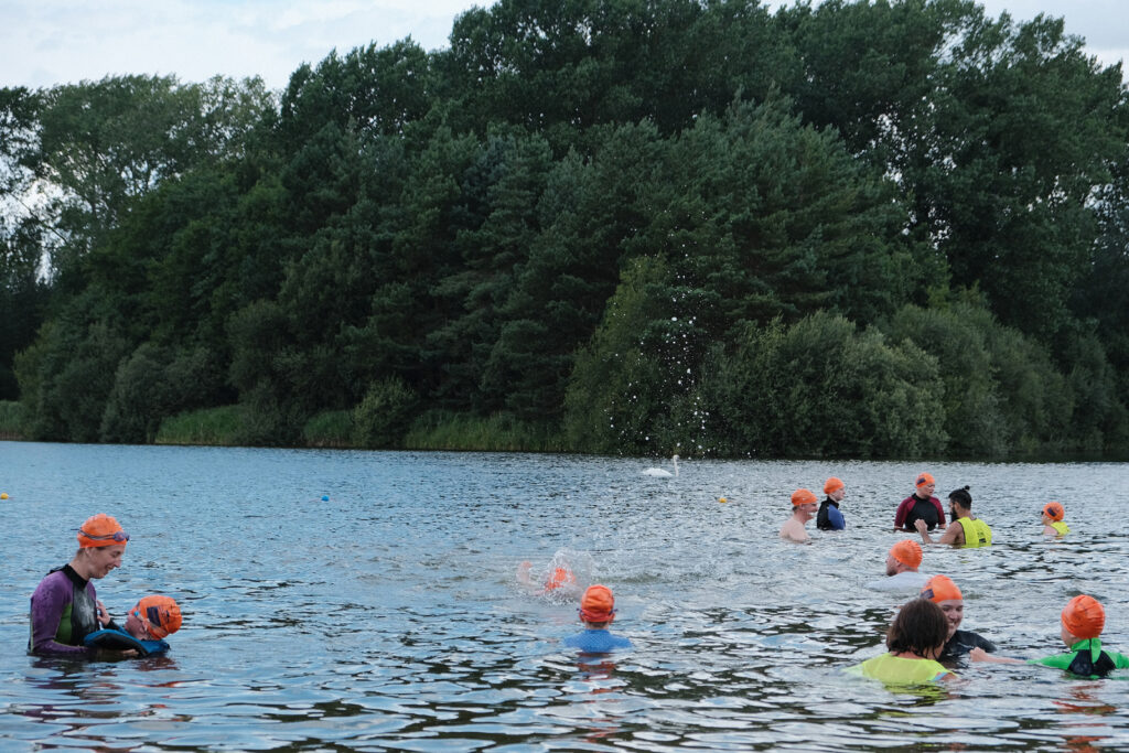 swimmers in water with volunteers