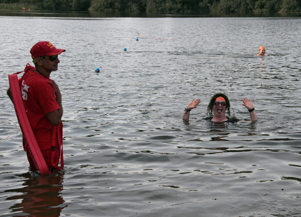 swimmer in water with lifeguard