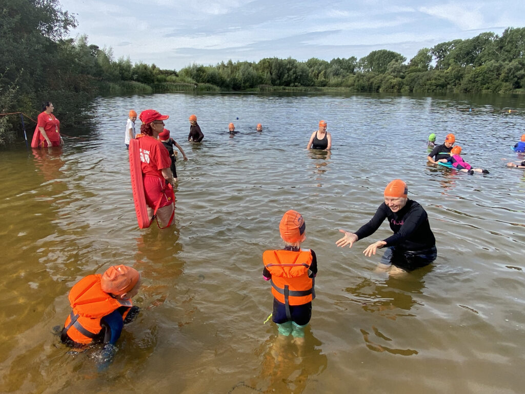 children and parents in water with lifeguards